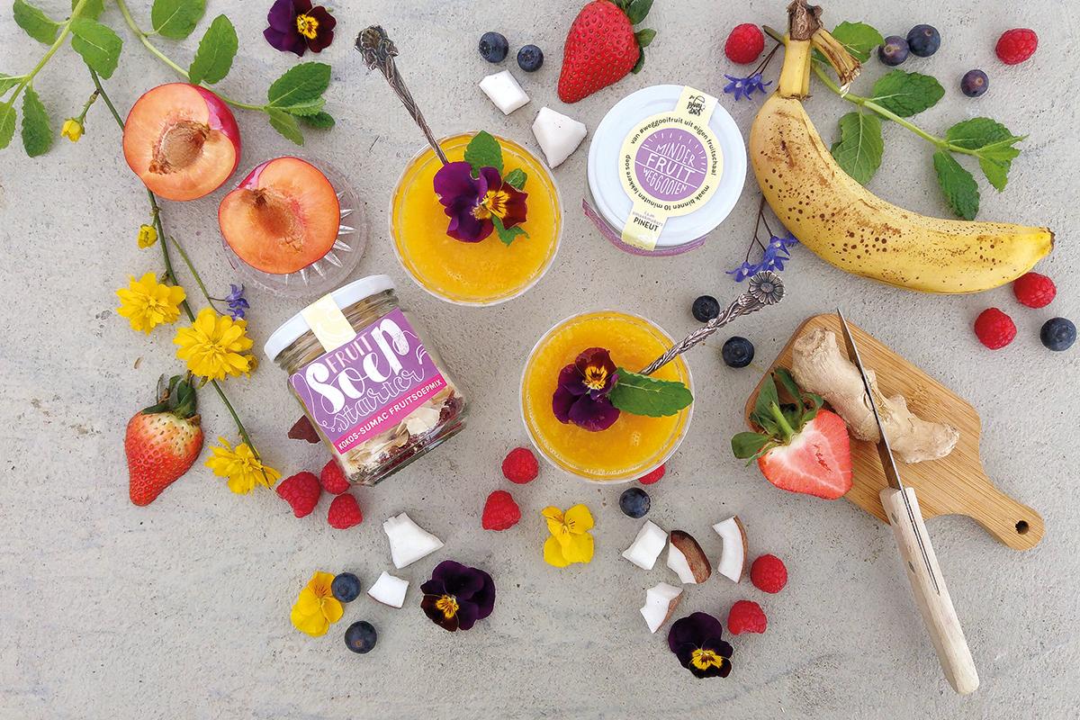 Potje FruitSoepStarter omringd met zomerfruit, als bessen, frambozen, aardbeien en banaan, waarmee je snel fruitsoep maakt. Met eetbare bloemetjes.